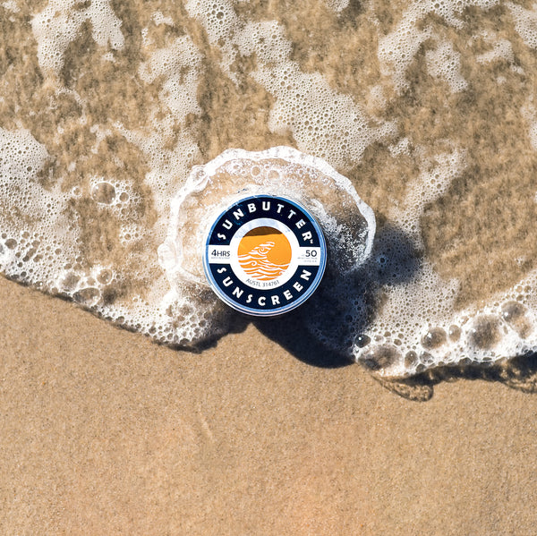 SunButter reef safe sunscreen: A tin of SunButter sits on the sand as a wave wraps around it