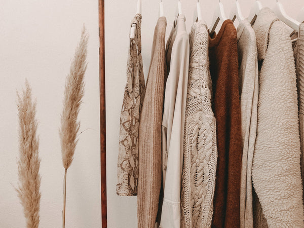 Microfiber pollution - an image of earthy-toned garments hanging from a clothes rack