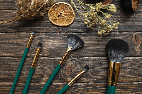Should you mix sunscreen and foundation? An array of make up brushes with green handles atop a wooden table