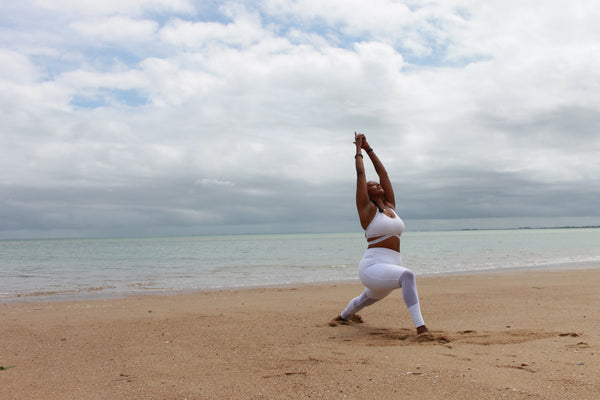 How Ayurveda is useful in modern life. A dark-skinned woman is on a beach wearing white yoga clothes and practicing a yoga pose where she is lunging with her arms above her head.