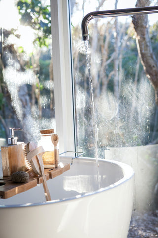 Winter skincare rituals - image of water running from a faucet into a deep white bath