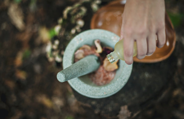 Ayurveda for skincare. A fair-skinned hand pours drops of oil into a mint-coloured mortar and pestle containing other ingredients, which are blurred out. The mortar and pestle is surrounded by greenery.