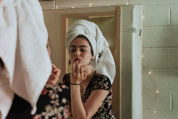 Winter skincare rituals - a woman with olive skin and dark eyebrows wears a towel on her head and applies lip balm in front of a mirror