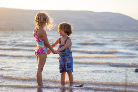 Best Sunscreen for Children. A small boy and girl stand opposite each other on a beach smiling and holding hands. In the background there are mountains