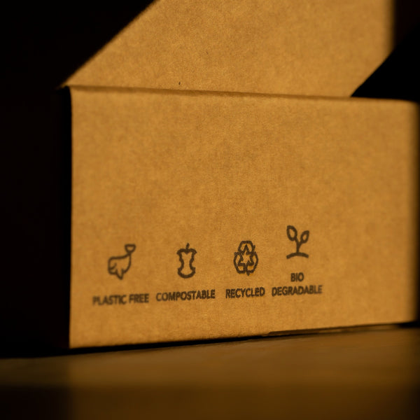 Our extra tips for Plastic Free July: A cardboard box with recycling, compostable, plastic free and biodegradable symbols on the side