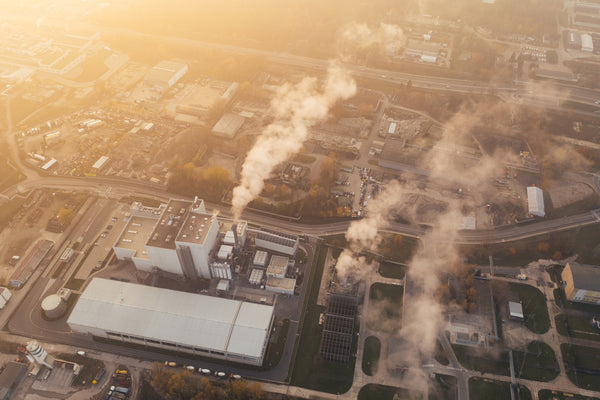 How can I reduce my emissions? An aerial shot of a factory releasing smoke