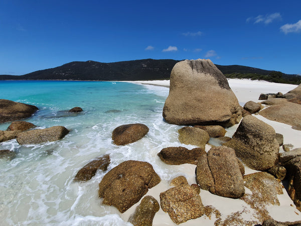 Our favourite places to wear SunButter sunscreen. Rocks and turquoise water at a beach at Wilson's Promontory.