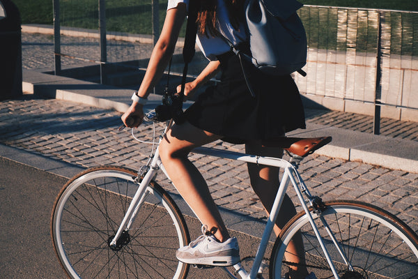 How can I reduce my emissions? A woman rides a bike in the sunshine