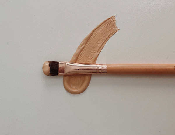 Should you mix sunscreen and foundation together? A make up brush on top of a smear of foundation on a white surface
