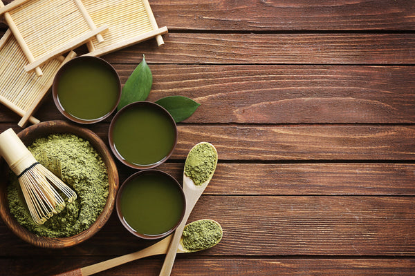 The lowdown on free radicals, antioxidants and your skin. An aerial image of traditional matcha tea powder and wooden instruments placed on a wooden table