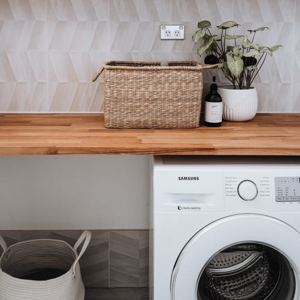 SunButter's extra tips for Plastic Free July: An image of a laundry with a timber benchtop, washing machine and baskets