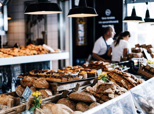 Why shopping local is important - image of breads and pastries stacked on countertop in cafe with staff in background