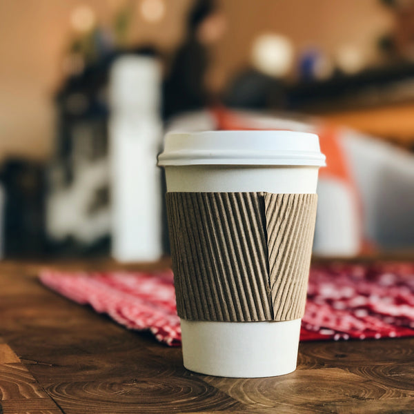 Our extra tips for Plastic Free July: A white takeaway coffee cup sits on a table