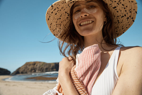 The lowdown on free radicals, antioxidants and your skin. A young woman stands on the beach wearing a straw hat and smiling with zinc across her nose