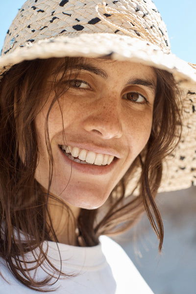 Tinted sunscreen - your questions answered. A young woman with olive skin and brown eyes and hair wear a sun hat and smiles at the camera.