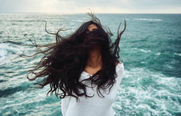 Windburn or sunburn? A woman with dark hair blowing across her face stands with the ocean in the background