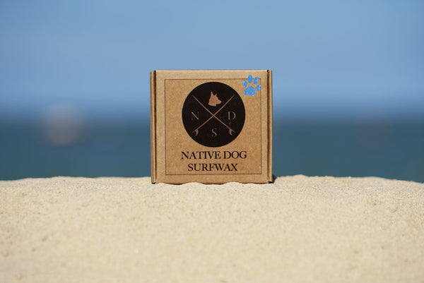 "Is surfboard wax toxic? An image of a small cardboard box that reads ""NATIVE DOG SURFWAX"" and has an image of a black circle containing a compass-like diagram and and a blue paw print sits on white sand with a blue sky in the background"