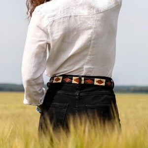 Femme de dos portant un look noir et blanc avec une ceinture de polo argentine dans les passants d'un jean noir. Femme seen from the back wearing black and white outfit with a polo argentinian belt in the loops of a pair of jeans.