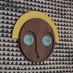 Décoration murale en bois, représentant un masque aux yeux jades et couronne jaune, en édition limitée par UMASQU. Wooden wall decoration, evoking an african mask with jade eyes and yellow crown made by UMASQU in limited edition.
