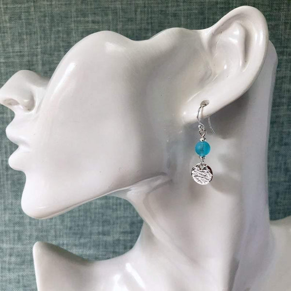Earrings with hammered sterling silver discs and turquoise-blue glass beads