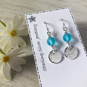 Drop earrings with frosted blue glass beads and hammered sterling silver discs