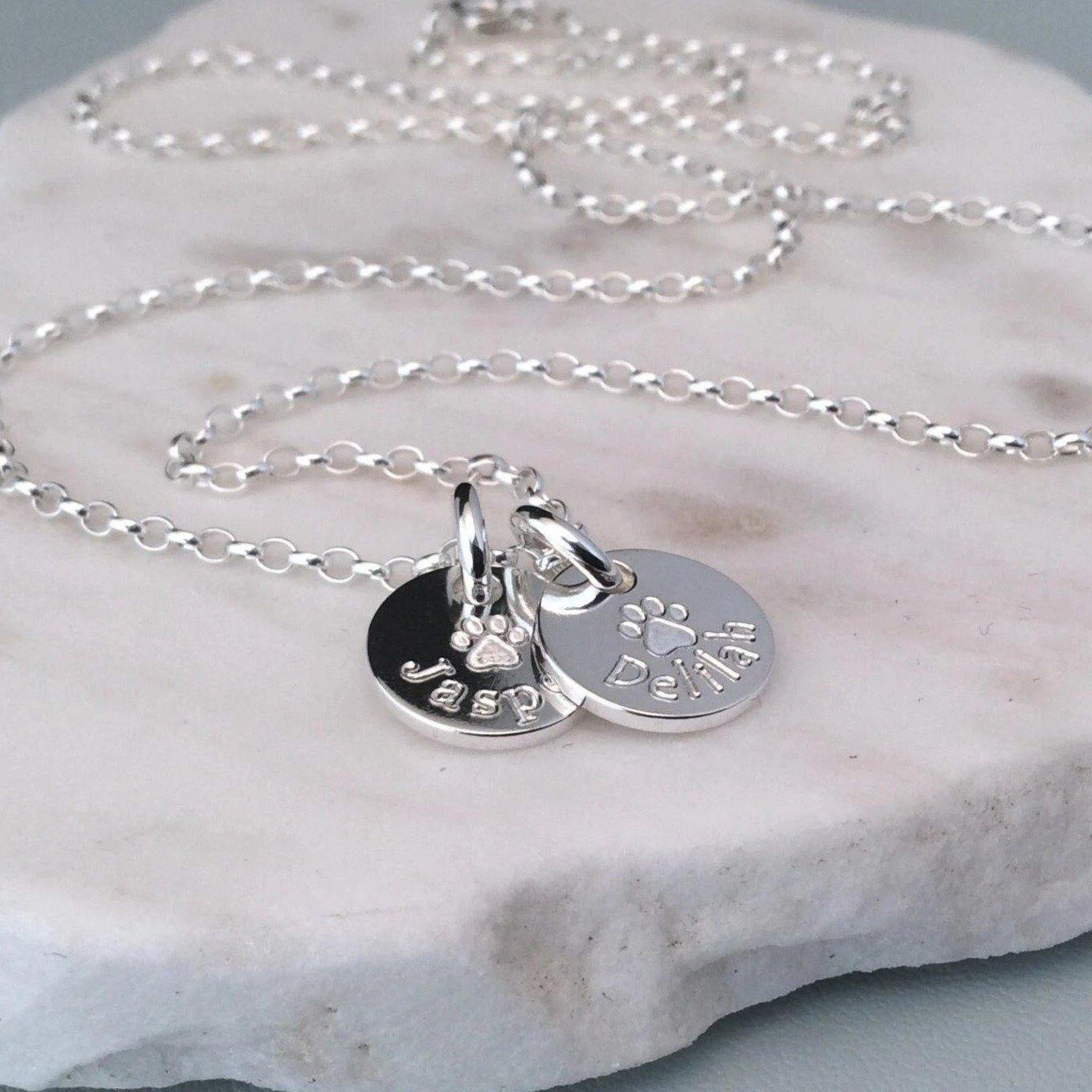 Paw print necklace with engraved paw print in centre and pets name underneath.  On tiny 1cm wide disc