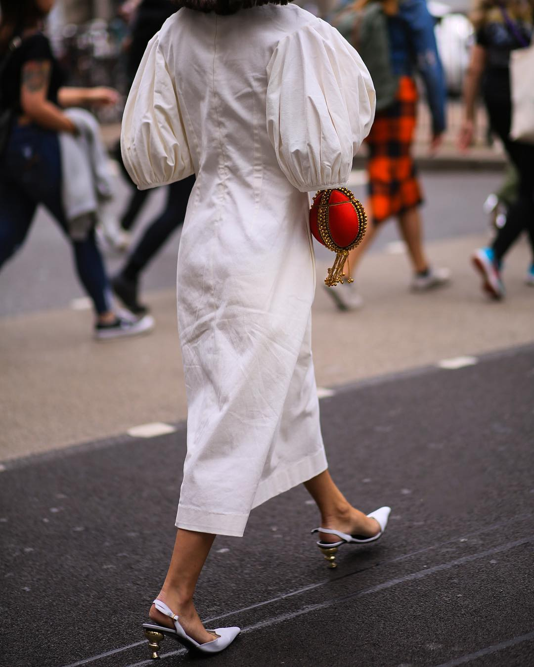 Anisa Sojka spotted at London Fashion Week wearing the fiery Red Babi Bracelet Clutch Bag. Photographed by David Nyanzi. Mae Cassidy Gold clutch bag street style LFW clutch bag red gold handbag occasionwear streetstyle with a white balloon sleeve EDIT dress and white Yuul Yie leather sling back