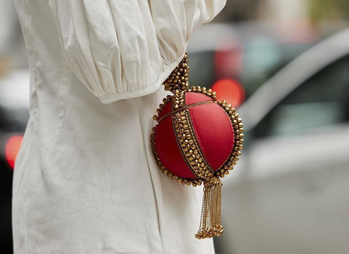 The Best Street Style Details Of London Fashion Week SS19 Anisa Sojka spotted at London Fashion Week wearing the fiery Red Babi Bracelet Clutch Bag. Photographed by David Nyanzi. Mae Cassidy Gold clutch bag street style LFW clutch bag red gold handbag occasionwear streetstyle with a white balloon sleeve EDIT dress and white Yuul Yie leather sling back