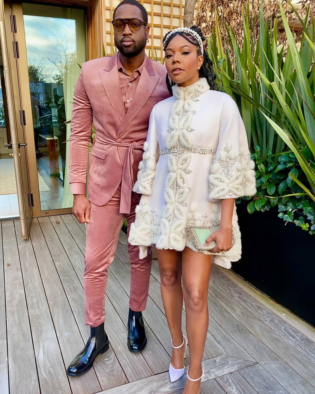 Hollywood American actress voice artist activist author Gabrielle Union attended the Ralph & Russo Paris fashion week show  husband American former professional basketball player Dwyane Wade Mae Cassidy, Botanical Mint & Silver Zeenat Clutch bag handbag ⁣Stylist Thomas Christos styled intricately detailed white couture Ralph & Russo cape dress Lilac court shoes Kenneth Soh Makeup and Hair pearl detail headband pink velvet layered look tie-waist slim-fit trouser suit shirt white socks black leather pull-on boots sunglasses. Botanical Mint Moonstone Lilac Coral Dreams Power Pink silver antique gold
