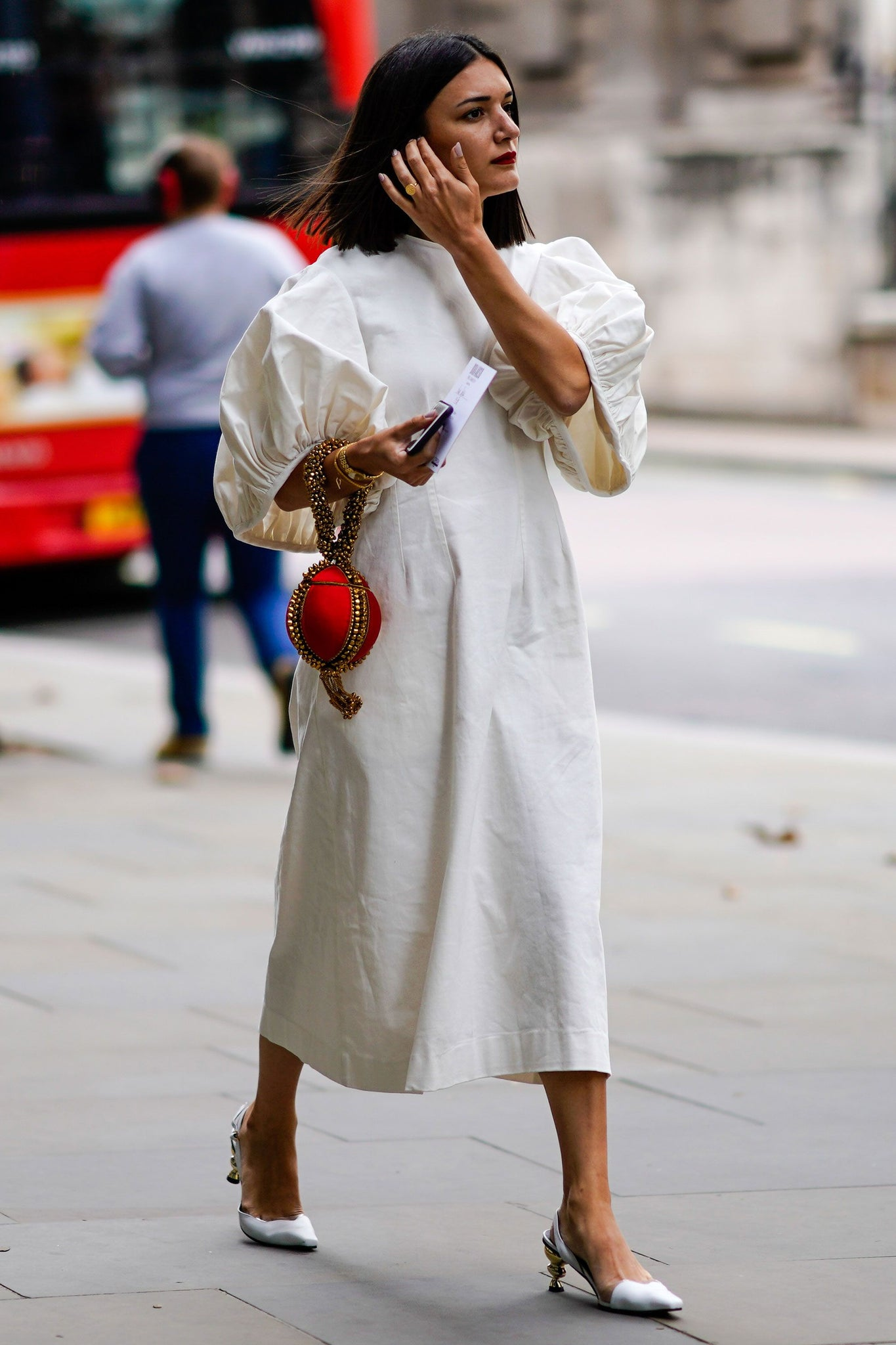 The Best Street Style Details Of London Fashion Week SS19 Anisa Sojka spotted at London Fashion Week wearing the fiery Red Babi Bracelet Clutch Bag. Photographed by David Nyanzi. Mae Cassidy Gold clutch bag street style LFW clutch bag red gold handbag occasionwear streetstyle with a white balloon sleeve EDIT dress and white Yuul Yie leather sling back Harper's Bazaar unusual dainty accesories make all the difference when it comes to dressing up a simple frock