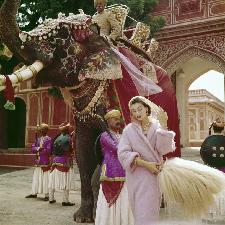 Norman Parkinson India British Vogue 1957 Anne Gunning in a pink mohair coat outside the City Palace, Jaipur, India, Vogue. 1956.