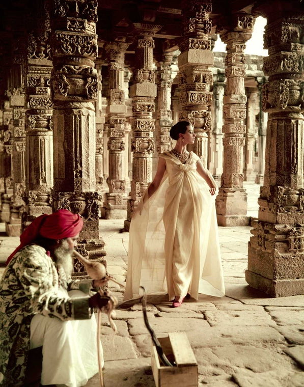 Norman Parkinson India British Vogue 1957 The Pillars of Quwwat-Ul-Islam Mosque at dusk, India, Vogue. Barbara Mullen wearing a gold lame Ball gown by Christian Dior. 1956