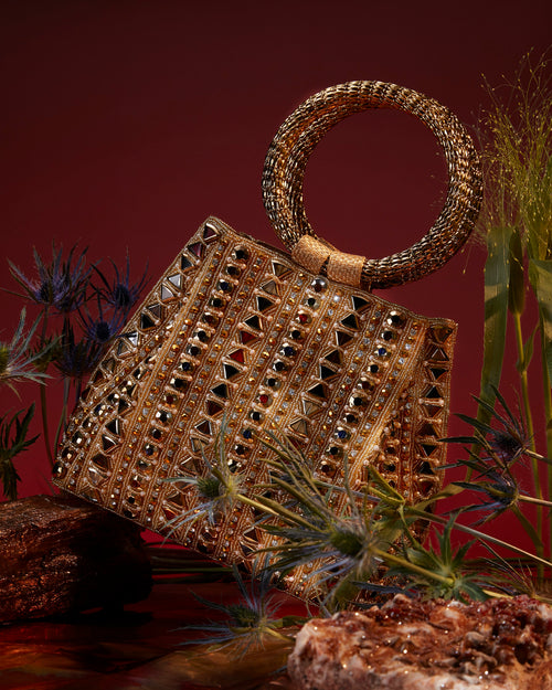 SHOP Mae Cassidy - The intricately crafted, Rekha Reflect handbag; handmade from mosaic jewelled beading and shimmering crystal embellishments. The circular hoop bracelet handle is precisely welded together from intricate pieces of gold-tone metalwork. Style with the cross-body strap or handheld to elevate any look.