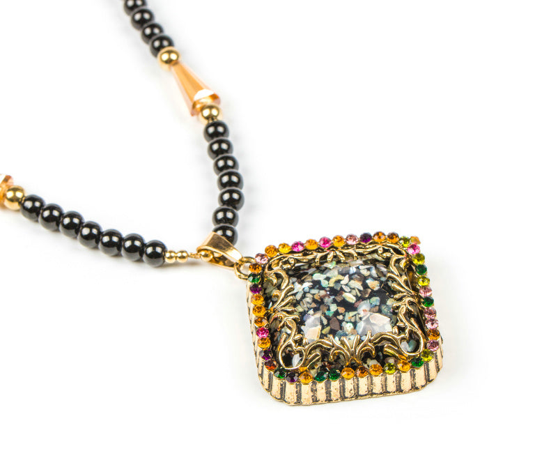 A lovely beaded necklace adorned with an ornate pendant with gold and shell accents. A beautifully unique piece.