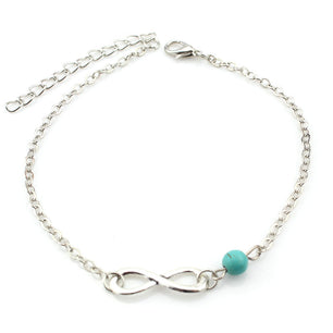 A single chainlink anklet detailed with a turquoise stone and infinity loop charm. In gold and silver.