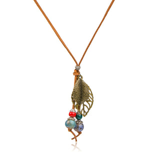 Leaf-shaped pendants accompany ornate ceramic beads in this beautiful bohemian necklace.