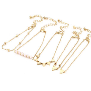 Chic and simple gold link bracelets in a set of five feature pink pearls, triangles and more. Super cute.