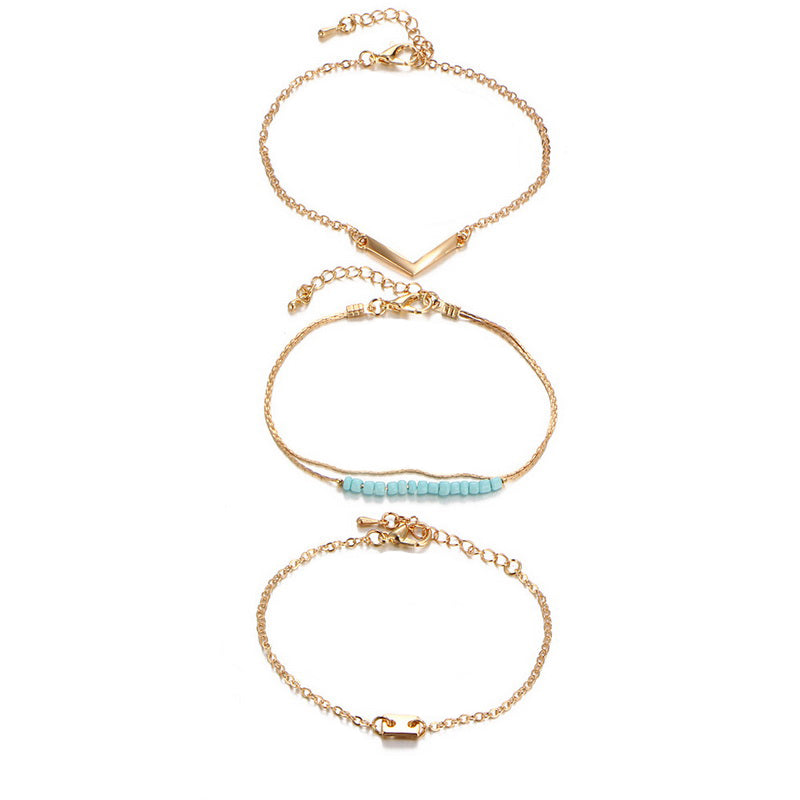 Three bracelets cast in gold, adorned with turquoise. Designed to be worn in a set or separate.