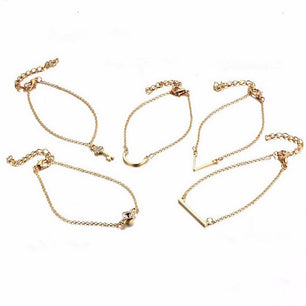 Gold cast bracelet set in elegant shapes from bars to keys. Layer for a bohemian look, wear separate for instant elegance.