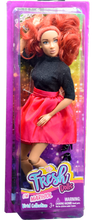 red hair fashion doll wearing black shirt and red/pink skirt boxed