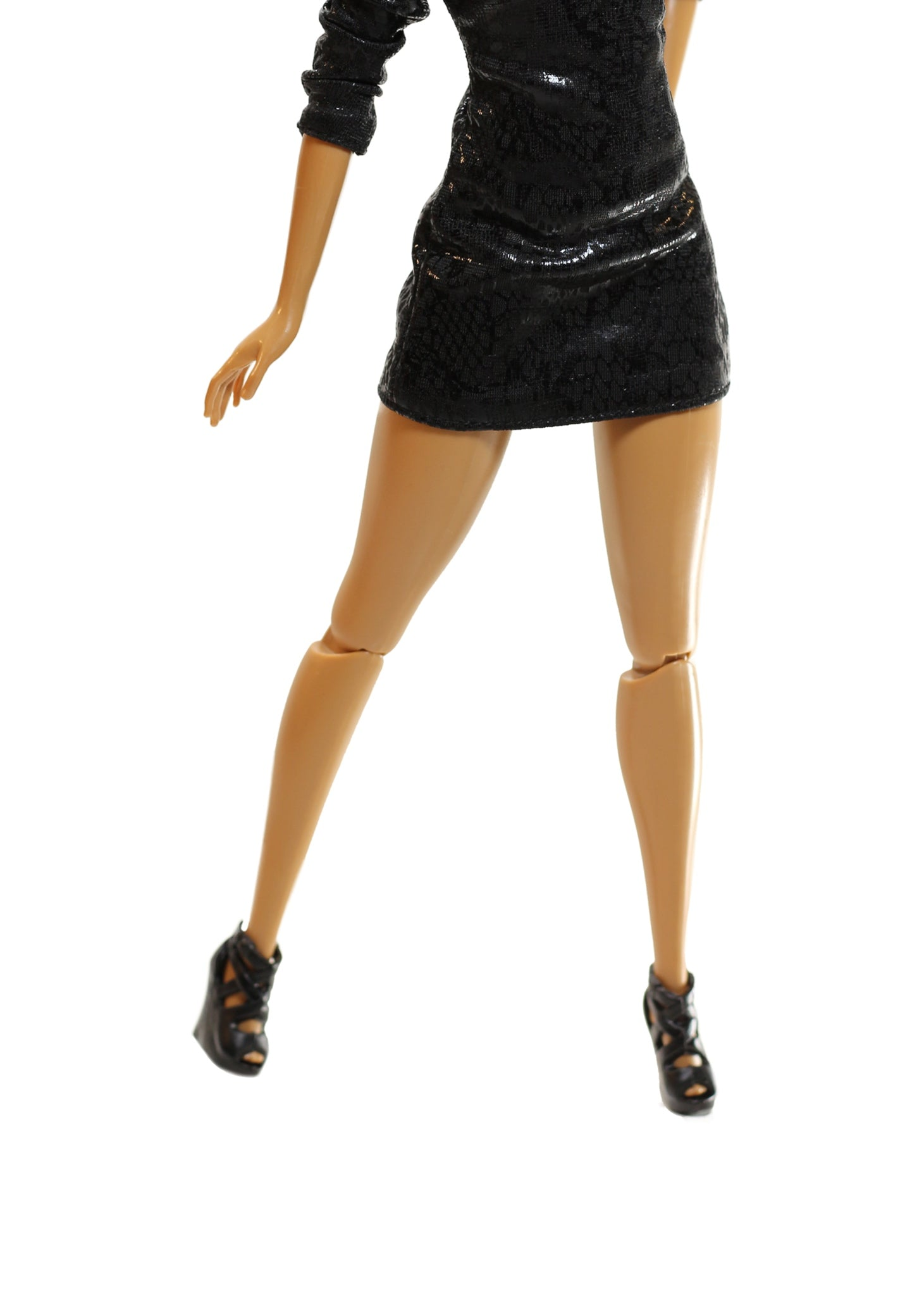 A fashion doll with black dress and black high heel.