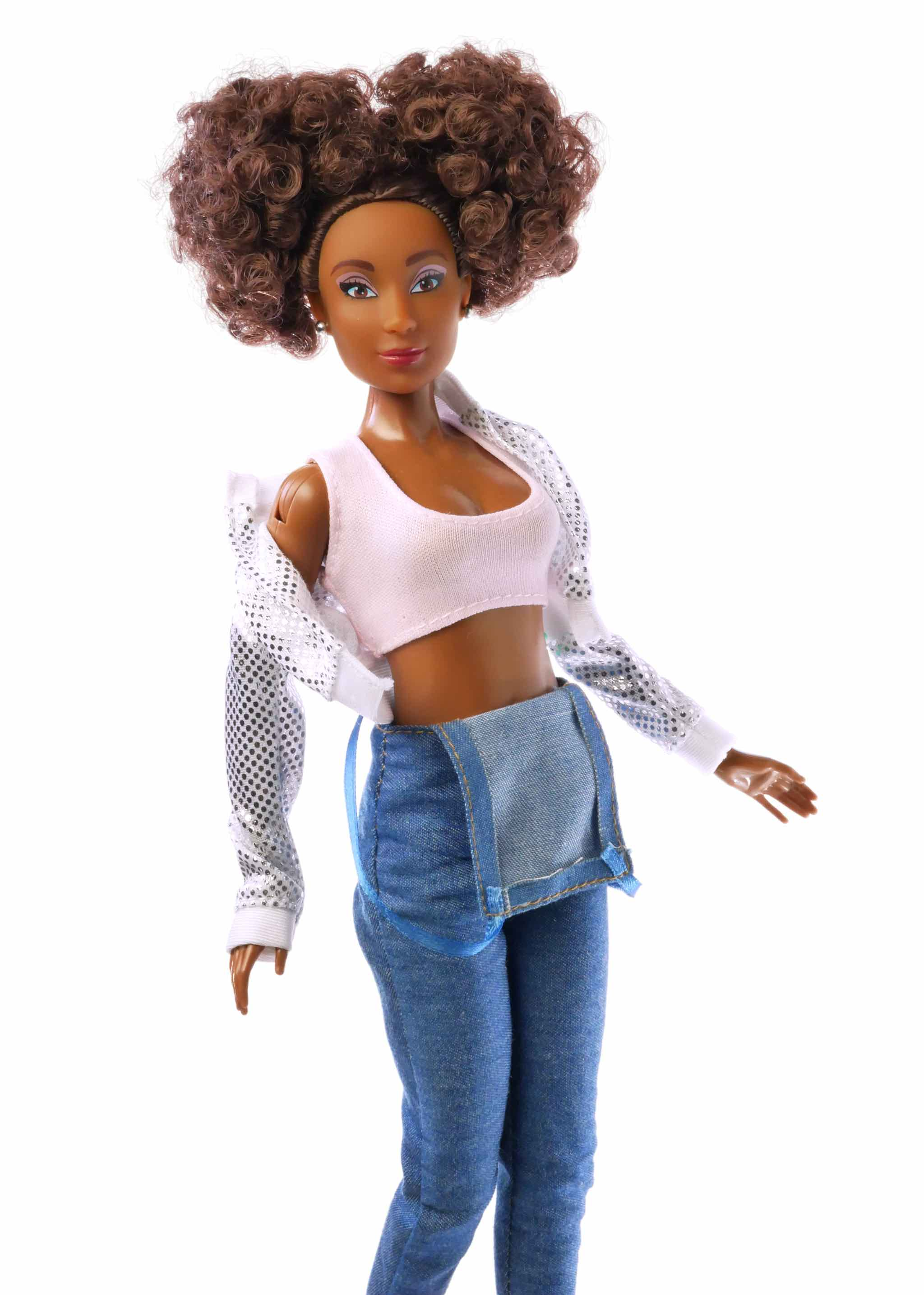 up close curly brown hair fashion doll wearing silver jacket pink top and camo shorts