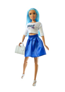 blue haired fashion doll wearing white top with sleeves and blue skirt holding white purse