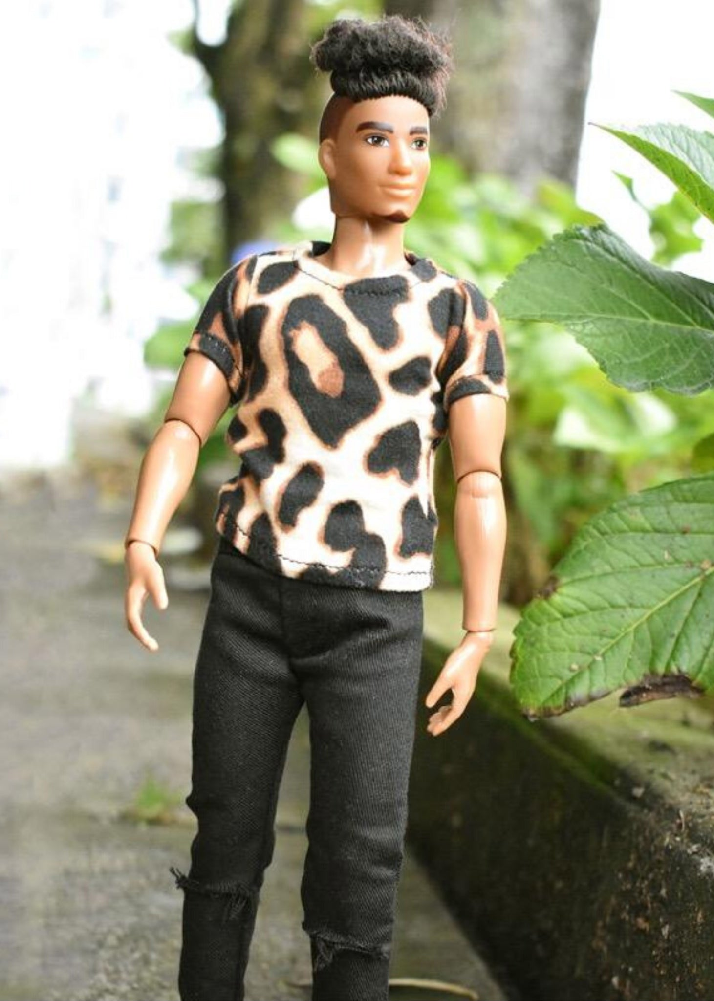 a male doll wearing hole jeans and animal print shirt.