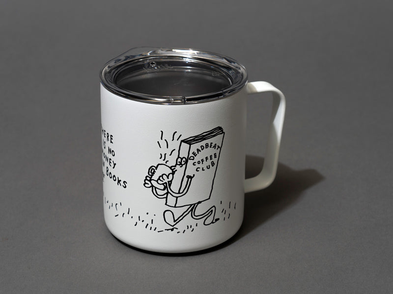"Close up, lid on. Insulated coffee cups featuring wrap-around illustrations by artist Stefan Marx. A book drinking a cup of coffee and a coffee mug reading a book. ""There's no money in books."" ""Deadbeat Club Coffee"" ""Deadbeat Club"""
