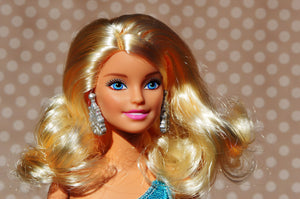 Image of Barbie Doll from shoulders up, with fake synthetic blonde hair. Illustrating how synthetic hair would look with clip in hair extensions. At LUSHIERE we only sell clip in hair extensions made of real human hair.