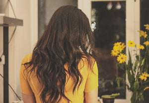 Brunette with long hair wearing yellow top