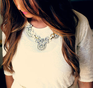 Image of beautiful brunette with long brown hair with chestnut highlights, illustrating what could be possible using LUSHIERE clip in hair extensions. Model is looking down and wearing an ornate necklace, white top and pink lipstick.