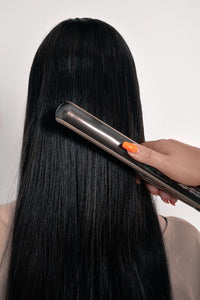 Image of someone using hair straighteners on long black hair showing how LUSHIERE clip in hair extensions can be heat styled