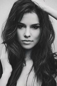Black and white image of gorgeous brunette looking straight at the camera with long dark hair. Illustrating natural full bodied volume that can be achieved with LUSHIERE CLIP IN HAIR EXTENSIONS